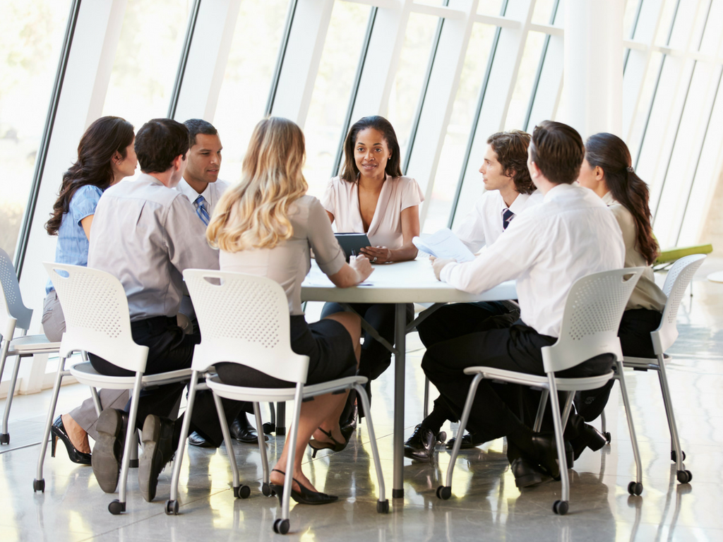 employees in meeting around a conference room desk
